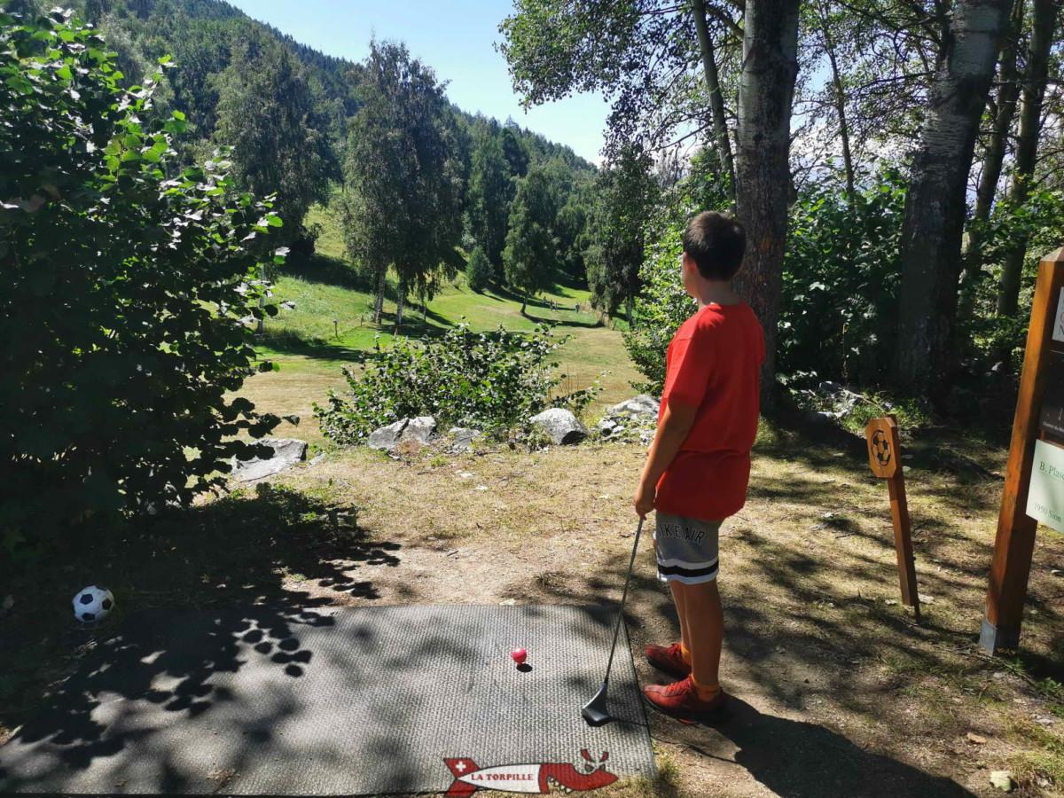 """Un joueur de swin golf au début d'un parcours à Nax avec la balle surélevée par un """"tee""""."""