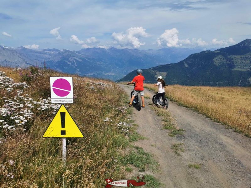 Des panneaux indicateurs rose indique le chemin à suivre.