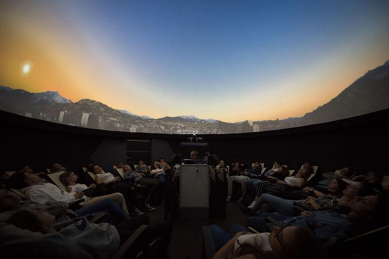 L'intérieur du planetarium de Sion. Le visiteur se trouve dans une position assise et allongée.