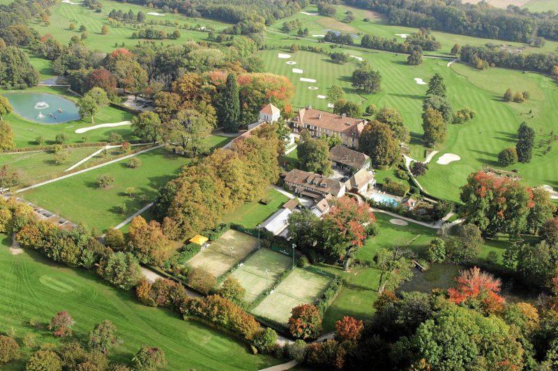 L'abbatiale à côté de laquelle se trouve des bâtiments hôteliers avec une piscine et autour de laquelle on peut voir les greens du golf.