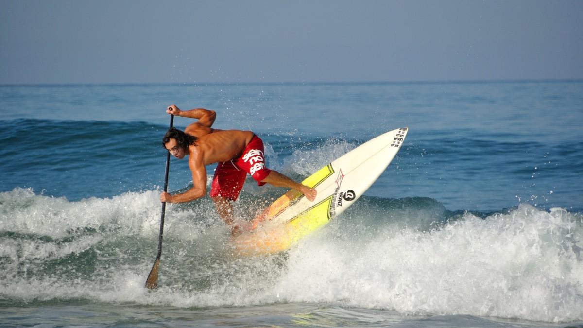 Un paddleur de compétition avec une planche de surf glissant sur un vague. P